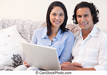 Couple with laptop on the sofa