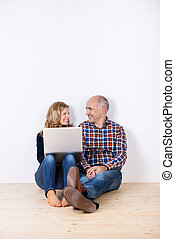 Couple With Laptop Sitting On Hardwood Floor At Home