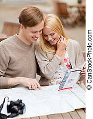 couple with map, camera and travelers guide