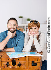 Couple With Map Leaning On Suitcase In House