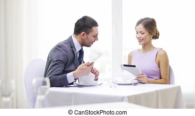 couple with menus on tablet pc at restaurant