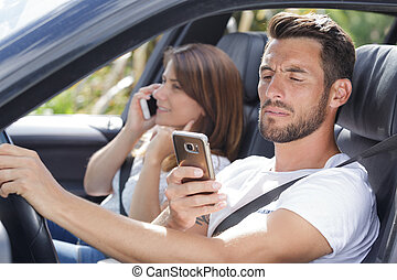 couple with mobile phone in car