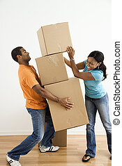 Couple with moving boxes. - African American female placing...