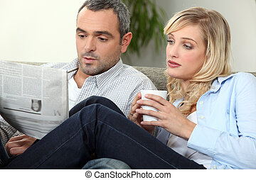 Couple with newspaper and coffee cup