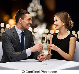 celebration, people and holidays concept - smiling couple clinking glasses of non alcoholic sparkling wine at restaurant over christmas tree background