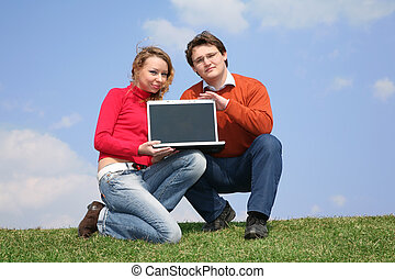 couple with notebook on meadow