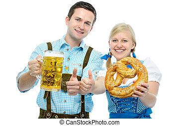 Couple with Oktoberfest beer steins and pretzel