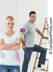 Couple with paint brush and ladder in a new house