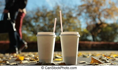Couple with paper coffee cups in autumn park