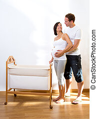 Couple with pregnant woman hug with baby cradle at home
