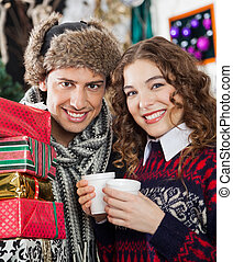 Couple With Presents And Coffee At Christmas Store