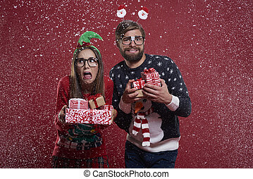 Couple with presents standing in the snow