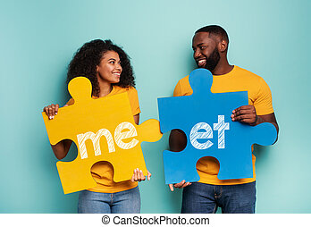 Couple with puzzles in hand over light blue background. Concept of integration, union, relationship and partnership