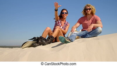 Couple with sand board sitting and pointing at a distance in the desert 4k