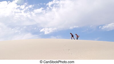 Couple with sand boards walking on the sand dune 4k - Couple...