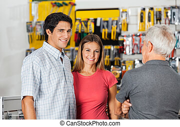 Couple With Senior Man In Hardware Shop