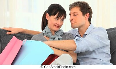 Couple with shopping bags on their sofa