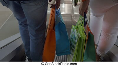 Couple with shopping bags riding escalator