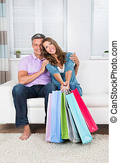 Couple With Shopping Bags Sitting On Sofa