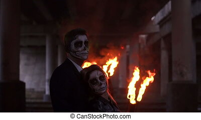 Couple with skull make-up on the background of burning fire and smoke. Halloween