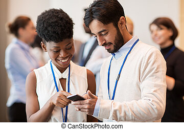 couple with smartphone at business conference