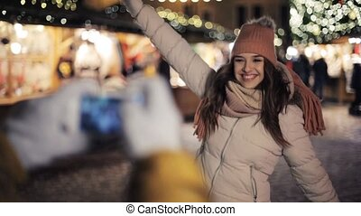 couple with smartphone photographing at christmas -...