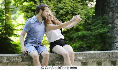 Couple with smartphone sitting on concrete wall taking...
