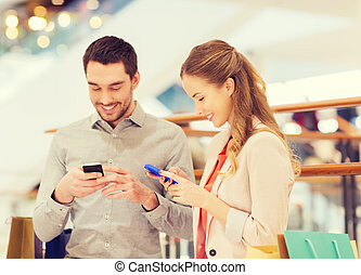couple with smartphones and shopping bags in mall - sale,...