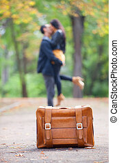 Couple with suitcase kissing at alley in the park