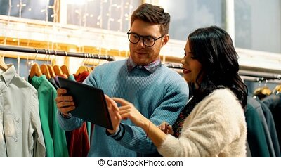 couple with tablet computer at clothing store