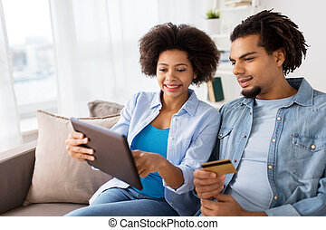 couple with tablet pc and credit card at home
