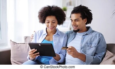 couple with tablet pc and credit card at home - family,...