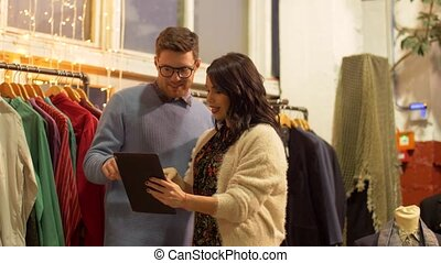 couple with tablet pc at vintage clothing store - sale,...