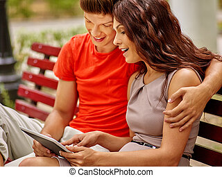 Couple with tablet pc sit on bench .