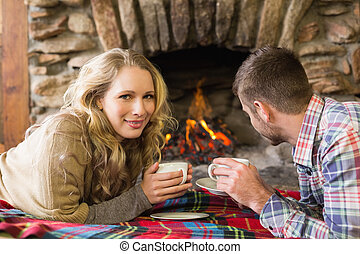 Couple with tea cups in front of lit fireplace - Side view...