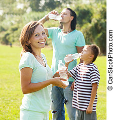 couple with teenager drinking water from bottles
