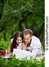 Couple with the laptop in park