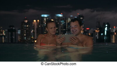 Couple with touch pad in rooftop pool at night