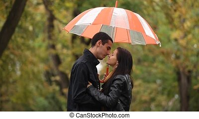 couple with umbrella kissing outdoo