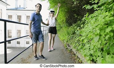 Couple with VR goggles on a walk in town. - Beautiful young...