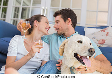 Couple with wine glasses and pet dog in living room