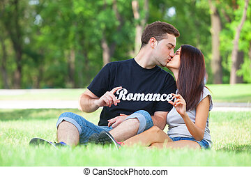 Couple with word romance in the park.