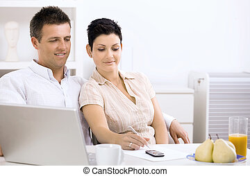 Couple working at home office, planning on paper.