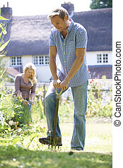 Couple Working In Garden At Home Together
