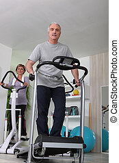 Couple working out on treadmill and cycle machine