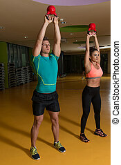 Couple Working Out With Kettle Bell
