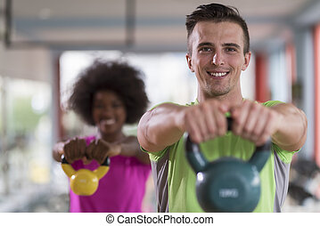 couple workout with weights at crossfit gym - healthy couple...