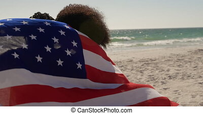 Couple wrapped in American flag sitting together on the beach 4k