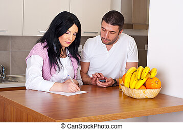 Couple writing and calculate their expenses - Serious mid ...