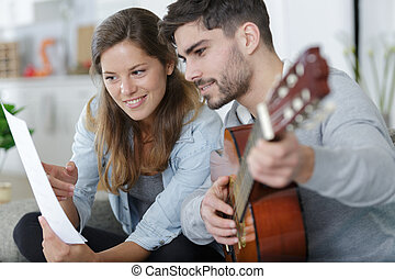 couplelearning how to play guitar
